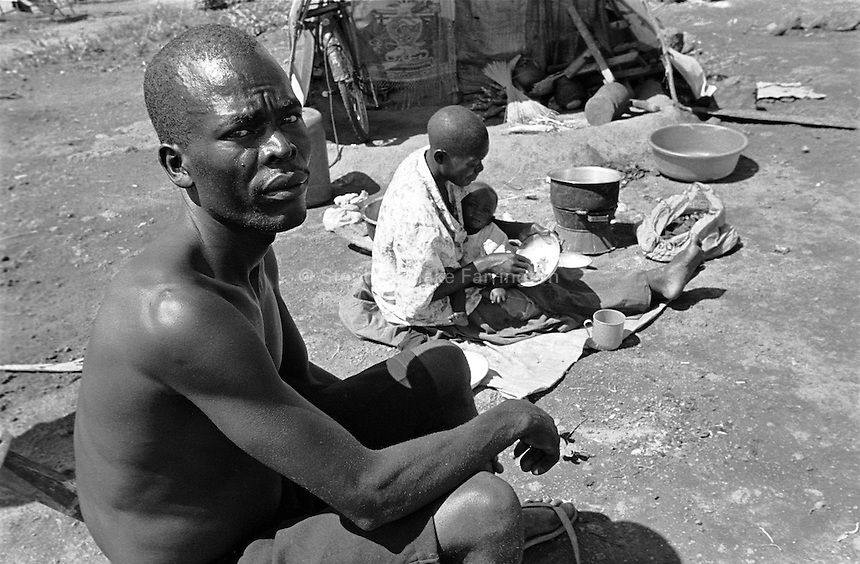 Man with his wife and child in the Erute Internally Displaced PeopleÕs (IDP) camp. The IDP camps of Northern Uganda formed when areas in the region became unsafe for civilians to live. Clean water, sanitation, food, employment, education, moral living, and human rights have almost been entirely depleted. Furthermore, congestion within the camps has contributed to major health and living problems. With 1.6 Ð 2 million people displaced and with an almost total lack of resources to care for them, the local peopleÕs very existence physically, emotionally and culturally is at stake. The war between the LordÕs Resistance Army and the Ugandan military has been transpiring since 1986. Thousands have been killed and abducted. Lira, Lira District, Uganda, Africa. July 2004 © Stephen Blake Farrington
