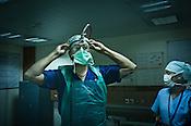 58 year old heart surgeon, Dr. Devi Prasad Shetty puts on his magnifying glasses as he gets ready for an open heart surgery at the Narayana Hrudayalaya in Bangalore, Karnataka, India. Photo: Sanjit Das/Panos