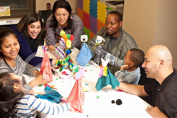 Parenting skills program offered by Headstart site to support families parent and child pairs music therapist occupational therapist psychologist working together on puppet craft activity
