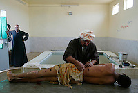 Iraq: Najaf: March 3, 2004: Ali Hadi, a professional body washer, prepared the body of a bombing victim for proper Muslim burial in Najaf while the man's relatives watched.