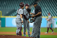 Home plate umpire Joe Harris has a meeting on the mound with Mississippi State Bulldogs starting pitcher Jacob Billingsley (45) and catcher Dustin Skelton (8) during the game against the Sam Houston State Bearkats during game eight of the 2018 Shriners Hospitals for Children College Classic at Minute Maid Park on March 3, 2018 in Houston, Texas. The Bulldogs defeated the Bearkats 4-1.  (Brian Westerholt/Four Seam Images)