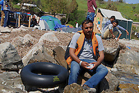 Mytilini / Lesbos / Greece 060416<br /> A refugee just landed on the island of Mytilini is resting on the rocks with a life jacket worn during the crossing between the Turkish and Greek coast.<br /> Photo Livio Senigalliesi