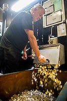 Tuesday 28 February 2017<br /> Pictured: A worker releases the newly struck pound cones from the machine <br /> Re: The Royal Mint in Llantrisant is producing the new one pound coin