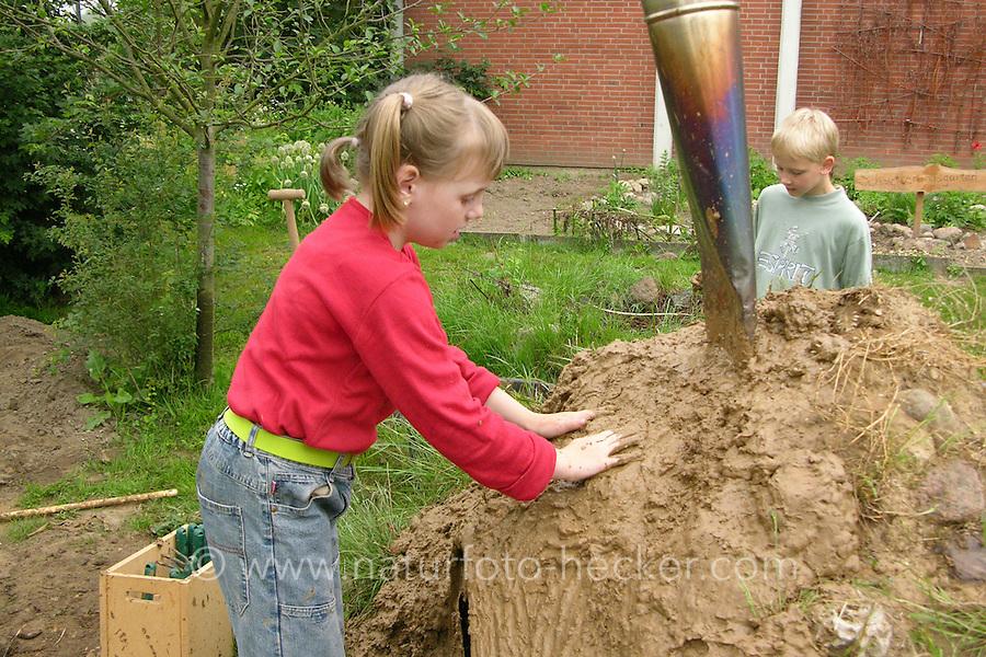 Lehmbackofen im Schulgarten, Garten der Grundschule Nusse wird als Projektarbeit von einer 1. Klasse gestaltet, Kinder bringen feuchten Lehm an einem Lehmbackofen an, Gartenarbeit