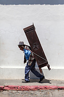 Antigua, Guatemala.  Laborer Carrying Furniture on his Back, Rope Around his Forehead.