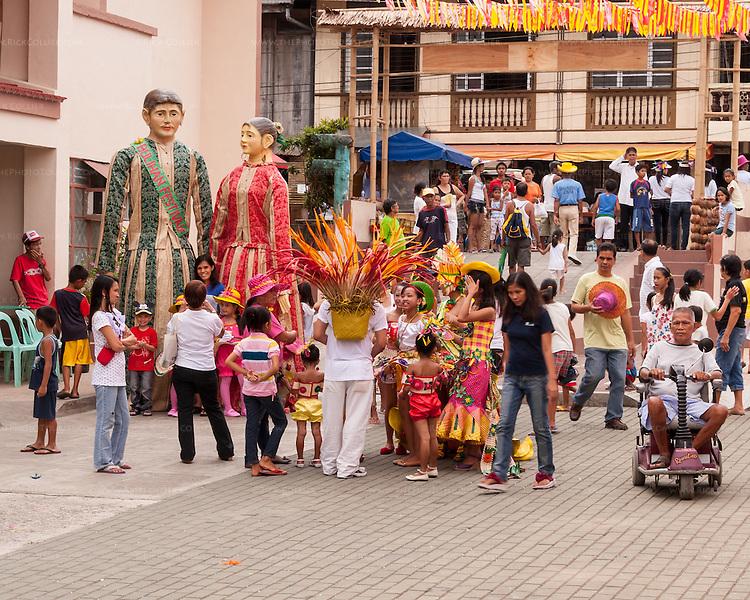 Locals arrive at Sampaloc's central municipal plaza as the Bulihan Festival begins.  (Sampaloc, Quezon Province, the Philippines.)