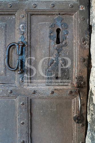 England. Old wooden door with big keyhole and metal handles.