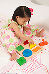 18 month old toddler girl playing with shape sorter toy vertical