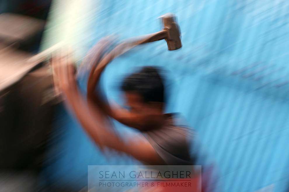 A recycling worker uses a hammer to break down electronics in a market in central Kolkata, India. November, 2013