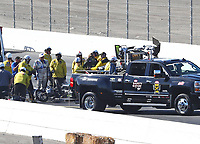 Feb 11, 2018; Pomona, CA, USA; NHRA funny car driver John Force (left) looks on as the safety safari rescue crews tend to his daughter, top fuel driver Brittany Force after crashing during round one of the Winternationals at Auto Club Raceway. Mandatory Credit: Mark J. Rebilas-USA TODAY Sports