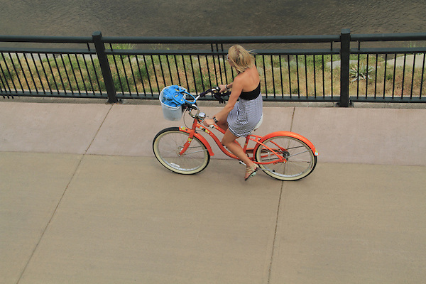 Woman riding her fat-tire bike on a sidewalk in Denver, Colorado. .  John offers private photo tours in Denver, Boulder and throughout Colorado. Year-round.