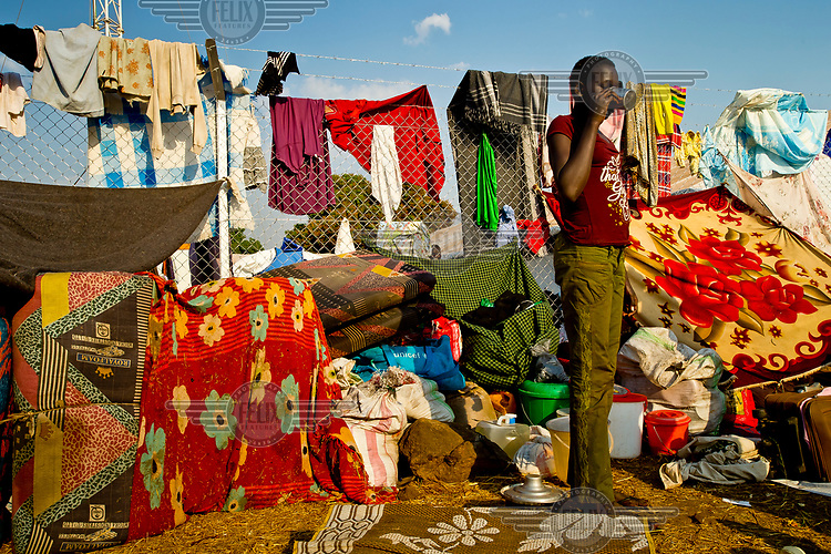 A young South Sudanese refugee drinks water while standing in the place his family has settled, as they wait to be relocated. They have piled up their belongings along the fence which separates Dzaipi I and Dzaipi II.