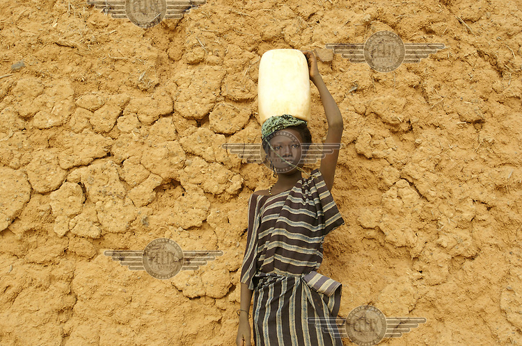 A girl stands with water on her head in the village of Intedeyne.