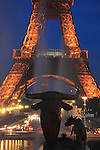 A closed up twilight view of Eiffel Tower with the fountain statues in Jardins Trocadero in foreground. City of Paris. Paris. France