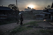 As the sun rises in the distance, a woman sweeps up to clean the area outside her house in Relocation Golden Valley in Barangay Pagkakaisa outside of Puerto Princesa, Palawan in the Philippines. <br /> Photo: Sanjit Das/Panos for Greenpeace