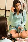 teenage girl 12 years old in bedroom looking at self in mirror putting on makeup vertical