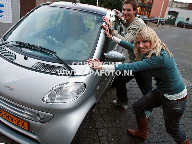 Nijmegen 200107 Nicole de Vries en Marc Schicks proberen hun Smart om te duwen, waarmee ze donderdag bij de storm door de politie van de weg werden gehaald.<br />Foto Frans Ypma APA-foto