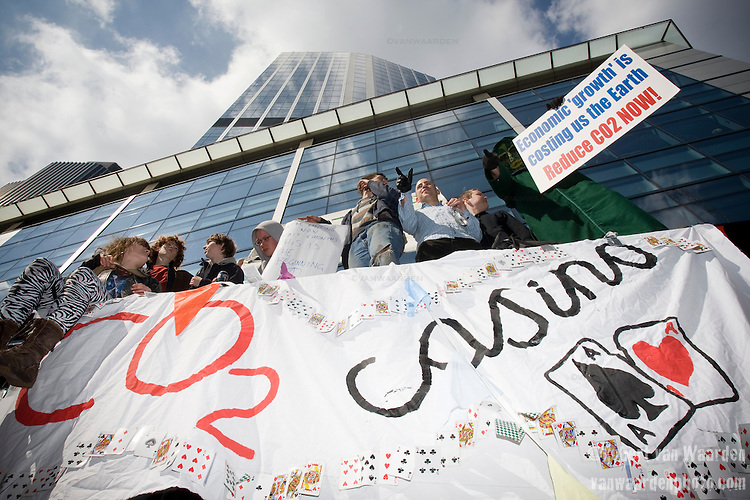 Activists stand on top of a bus shelter with banners drawing attention to the correlation between the  climate and financial crises.