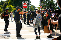 A Pittsburgh Police officer in riot gear threatens a protester with pepper spray as they take part in Civil Saturday that started in Market Square and marched through downtown before being met by Pittsburgh Police in riot gear near the Fort Pitt bridge on ramp on Saturday July 4, 2020 in Pittsburgh, Pennsylvania. (Photo by Jared Wickerham/Pittsburgh City Paper)