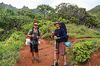 Two backpackers with walking sticks on the Kalalau Trail on Kaua'i, with one giving the shaka sign.