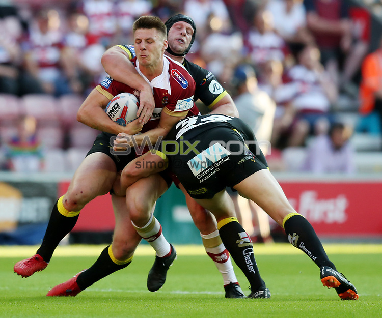 Picture by Paul Currie/SWpix.com - 06/07/2018 - Rugby League - Betfred Super League - Wigan Warriors v Warrington Wolves - DW Stadium, Wigan, England - Tom Davies of Wigan Warriors is tackled by Ben Westwood of Warrington Wolves and Chris Hill of Warrington Wolves
