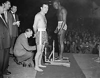 Boxers Bep van Klaveren and Idrissa Dione (France) on the scales, November 28, 1955,<br /> before the fight for the title.<br /> <br /> Photographer Pot, Harry / Anefo