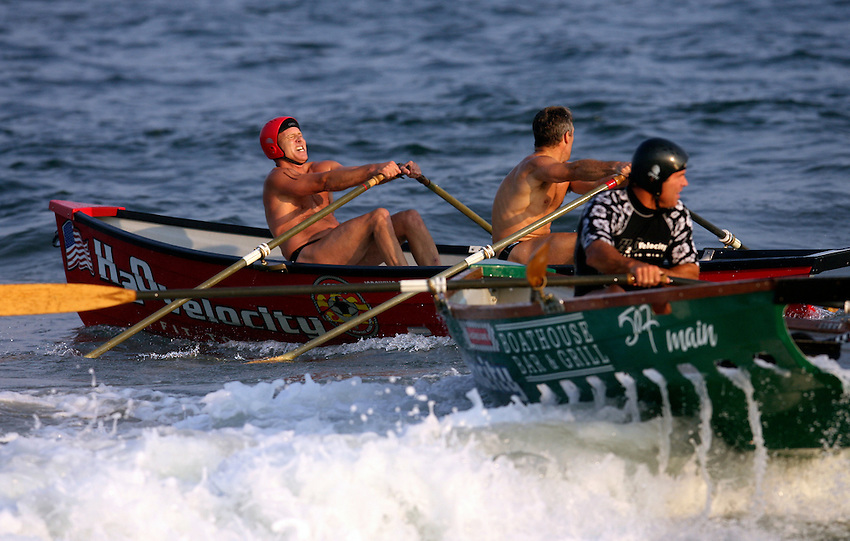 Dave Healy (left, in red boat) and partner Warren Towns pull together to pass Long Branch's Billy George in the 3,000-meter surfboat event at the First Annual Asbury Park Beach Bar Lifeguard Competition held at the 3rd Avenue beach in Asbury Park.  Healy and Towns placed first in this event. ASBURY PARK, NJ  8/4/07  8:21:47 PM  PHOTO BY ANDREW MILLS