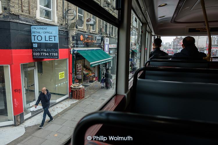 Empty shop on Kilburn High Road, London, from a bus window.