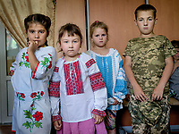 Darina Korol (6), Asya Malik (5) and Alina Alexeeva (6) wearing donated traditional Ukrainian folk costumes, while Yaroslav Koukoul (9) wears his own military-style outfit.<br /> <br /> Natalia Voronkova (not pictured) and her NGO 'Volonters'ka Sotnya Dobrovolya', wants to help the vulnerable children who are suffering during the war in the east of the country, and at the same time strengthen their national feeling with, among other things, these folk costumes. After an open call online people from all over the country have been sending in these Ukrainian folk costumes in children's sizes. Today, the many donated dresses and shirts are being handed out to the children at the Novhorodske orphanage, which is just three kilometres from the frontline. The military style outfit of Yaroslav Koukoul is not a part of Natalia's donations.