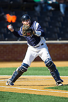 Georgetown Hoyas catcher AC Carter (13) checks the runner at first during the NCAA baseball game against the Marshall Thundering Herd at Wake Forest Baseball Park on February 15, 2014 in Winston-Salem, North Carolina.  The Thundering Herd defeated the Hoyas 5-1.  (Brian Westerholt/Four Seam Images)