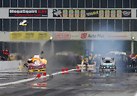 May 17, 2014; Commerce, GA, USA; NHRA funny car driver Tim Wilkerson (left) explodes an engine sending pieces of the carbon fiber body into the air alongside John Force during qualifying for the Southern Nationals at Atlanta Dragway. Mandatory Credit: Mark J. Rebilas-USA TODAY Sports