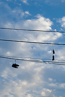 Silhouette of Shoes and Sneakers Hanging from Telephone Wires in the Williamsburg neighbohood of Brooklyn, New York City