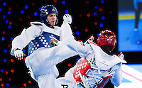 05 MAY 2012 - MANCHESTER, GBR - Aaron Cook (GBR) of Great Britain aims a kick at Ramin Azizov (right in red) of Azerbaijan during the men's 2012 European Taekwondo Championships -80kg final at Sportcity in Manchester, Great Britain .(PHOTO (C) 2012 NIGEL FARROW)