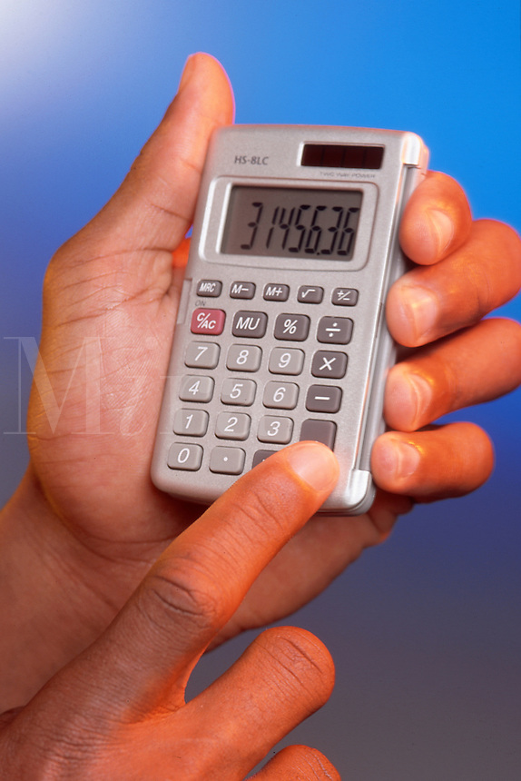 A hand holding a calculator.