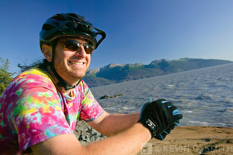 Middle aged man, caucasian, resting on his mountain bike after riding on the rocks along the shoreline, Turnagain Arm, Summer, Kenai mountains in the background, Southcentral Alaska, USA. MR.