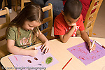Preschool ages 3-5 art activity boy and girl drawing side by side using opposite hands right or left to draw and hold markers horizontal