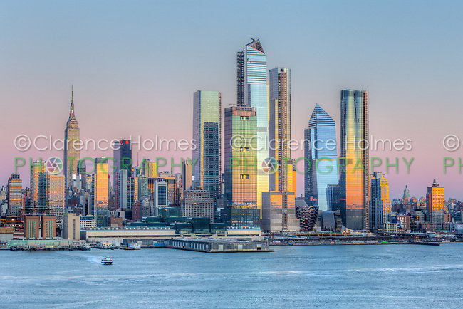 The mixed-use Hudson Yards real estate development and other buildings on the West Side of Manhattan in New York City.  The orange colored western sky adds beautiful reflections to the windows of the skyscrapers at sunset.