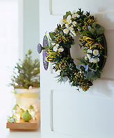 A door wreath that is both visually appealing and fragrant is easily made arranging greenery and flowers on an oasis wreath