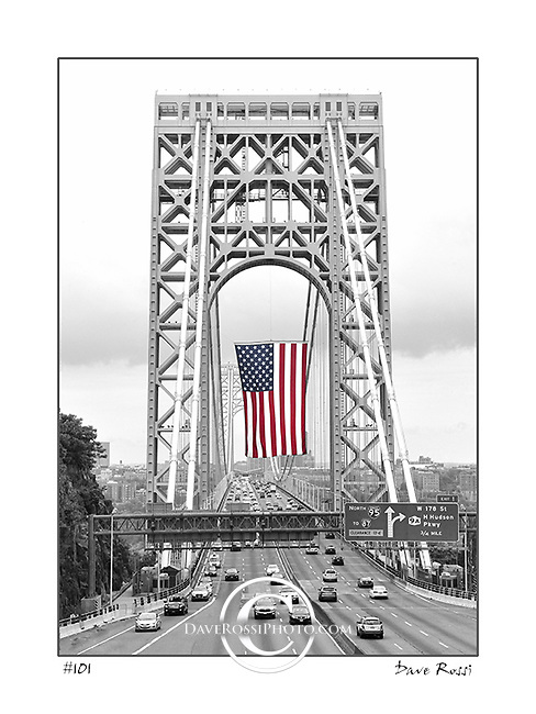 George Washington Bridge with the largest American flag deployed on July 4, 2015. This fine art image was taken by Dave Rossi from a dangerous location in Ft Lee, New Jersey facing New York City. Dave took this slightly off center so the east tower would be visible in the image. This limited edition print is beautifully printed in black and white on metallic paper with just the flag at center in color.<br /> The image is also available for tasteful and limited commercial stock uses.