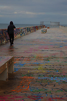 Bari: The dock in the historical center of the town, with a person taken from behind that is walking towards the see. The dock is colorful, because of its paintings and writings, and there is a suggestive open gate at its end.<br /> <br /> This photo is available only in Editorial.