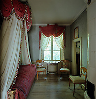 In the bedroom the bed hangings and matching curtains are in the style of the 1820s