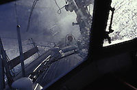 Sailing yacht 'Heron' in rough seas, with waves breaking over bow, seen through cockpit windows