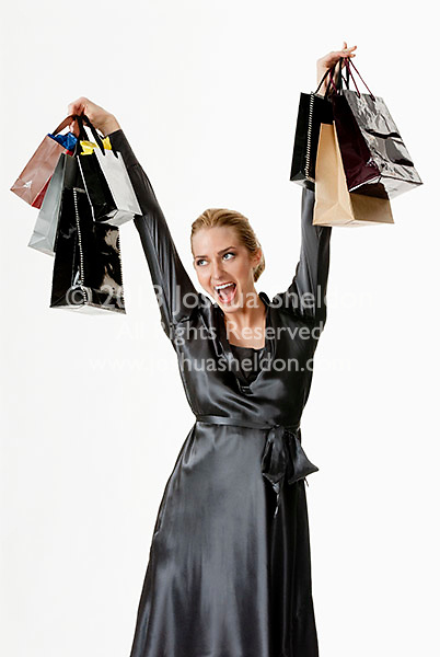 Young woman holding shopping bags above her head