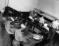 Instructor in class 4 at Naval School of Photography processing motion picture film.  Portable Stineman film processing outfits. This is not the best method, but will give usable results under field conditions  when speed in delivering the film to the briefing room is paramount, and the regular processing machines are miles away.