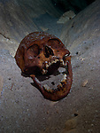 Ancient skull resting on the sandy bed of a cenote once used by the Maya