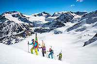 The Ortler Group in northern Italy is a popular region for spring ski touring using the huts for overnights to ski all the many peaks in the mountain group. Ski tourers climbing the Punta Pedranzini, 3599 meters, with their skis on their packs.