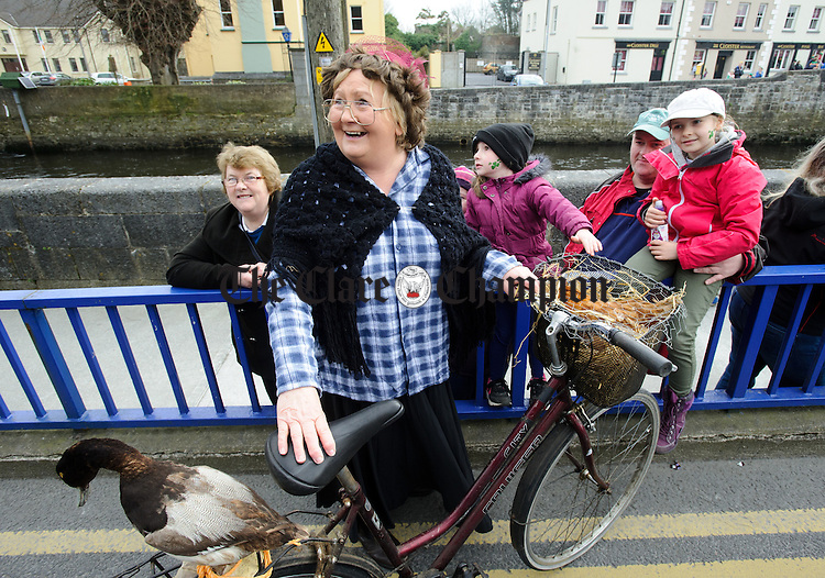 Ella from Ennis Tidy Towns with her fowl on board her bike during the St Patrick's Day parade in Ennis. Photograph by John Kelly.