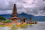 """The Hindu temple of Ulun Danu at Candikuning is one of the iconic images of Bali, Indonesia.  Located in the high hills of the Bedugul, about 30 miles north of Bali's capital city of Denpasar, the temple is built on the shores of the crater Lake Bratan (formed from the sunken crater of a long-dormant volcano).  Much of the inner precincts of the temple is closed to the (non-Hindu) public, but the gardens are spectacular and feature fabulous shrines, statuary, and views.  The iconic tourist image is the two """"water shrines,"""" which these days are usually partially submerged in the waters of Lake Bratan. (HDR image)"""