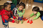 Preschool 4 year olds two boys and girl playing with magnets and Hulk Hogan action figure one boy brought from home