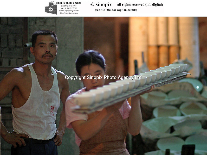 A Chinese worker moves a plank lined with porcelain ware at the Guangming Porcelain Factory in Jingdezhen, Jiangxi Province, China. The township of Jingdezhen is well known in China as the country's porcelain capital ever since it was selected exactly one thousand years ago as the royal porcelain provider for the imperial court..24-JUN-04